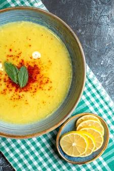 青の背景に半分に折り畳まれた緑のストリップタオルにミントと刻んだレモンを添えたおいしいスープが入った青い鍋の垂直方向の眺め