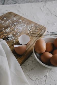 白い表面のまな板の横にある卵と銀の泡立て器のボウルの垂直方向のビュー