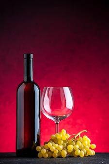 赤い背景の上の黄色ブドウとボトルガラスのゴブレットの束の垂直方向のビュー