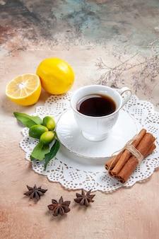 Вертикальный вид чашки черного чая на украшенной салфетке с фруктами корицы на красочном столе