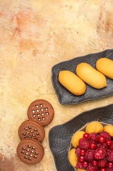 혼합 색상 배경에 갈색 접시 과일에 선물 케이크와 비스킷의 세로보기