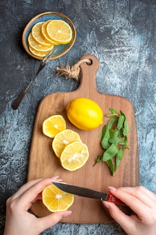 暗い背景に木製のまな板の上に新鮮なレモンとミントを刻む手の垂直方向のビュー