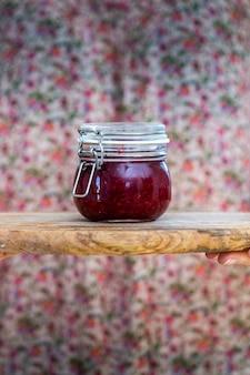 木製の表面のガラス瓶に自家製ビーガン生ラズベリージャムの垂直方向のビュー
