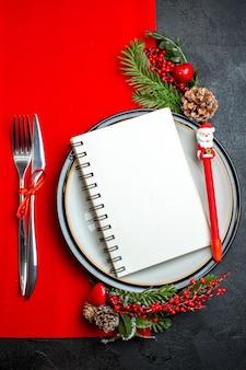 Вертикальный вид спиральной тетради и ручки на обеденной тарелке с декоративными аксессуарами еловые ветки и столовые приборы на красной салфетке