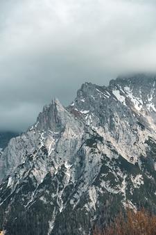 曇り空の下の背の高い山の垂直ビュー