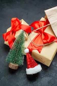 Вертикальный вид красивых подарков с красной лентой и новогодней шапкой санта-клауса на темном столе