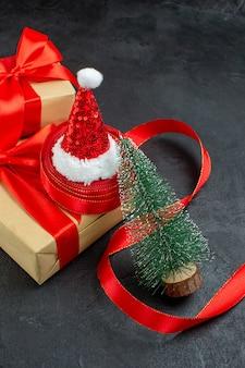 Вертикальный вид красивых подарков с красной лентой и новогодней елкой в шапке санта-клауса на темном столе