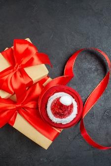 Вертикальный вид красивых подарков с красной лентой и шляпой санта-клауса на темном столе