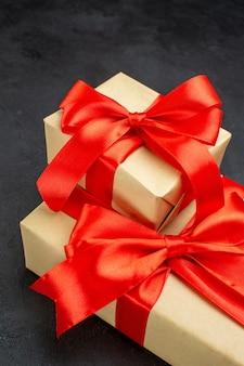 Вертикальный вид красивых подарков с красной лентой на темном фоне