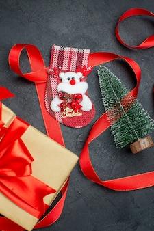 暗い背景の上の美しい贈り物xsmas靴下クリスマスツリーの垂直方向のビュー