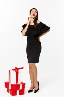 豪華なドレス、赤い唇と宝石、白い背景の上のクリスマスプレゼント、白い背景の上に立っている美しい若い女性の垂直方向のビュー。