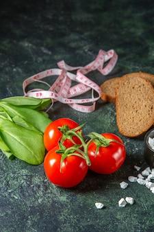 黒いパンの垂直方向のビューは、暗い色の表面に茎とメートルの緑の束の塩で新鮮なトマトをスライスします