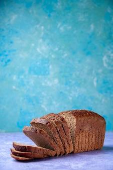 空き領域と水色のパターンの背景に黒いパンのスライスの垂直方向のビュー