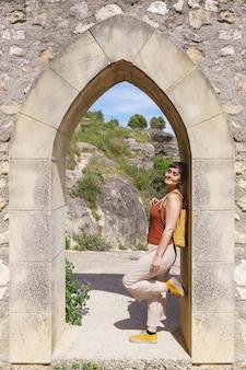고대 스페인 도시 쿠엥카에서 휴일에 짧은 머리를 한 백인 여성의 수직 전망. 유럽 도시에서 여행 배낭과 휴일 개념.