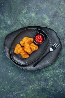 어두운 표면에 검은 접시에 치킨 너겟과 케첩 포크의 세로보기