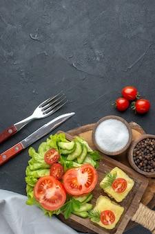 まな板に刻んだ新鮮な野菜チーズと黒い表面にセットされたスパイスカトラリーの垂直方向のビュー