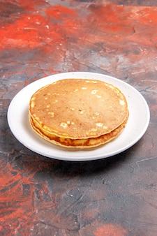 混合色の白いプレート上の古典的なアメリカのバターミルクパンケーキの垂直方向のビュー