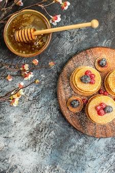 灰色のボウルに古典的なアメリカのパンケーキ蜂蜜の垂直方向のビュー