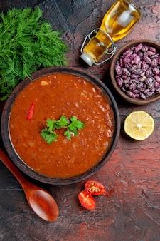 갈색 그릇에 클래식 토마토 수프의 세로보기 콩과 숟가락 기름 한 병