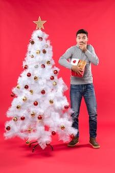 장식 된 흰색 크리스마스 트리 근처에 서 빨간색에 그의 선물을 들고 혼란 잘 생긴 남자의 세로보기