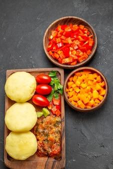 黒いテーブルの上で新鮮な野菜とみじん切りの食品を使った料理の垂直図