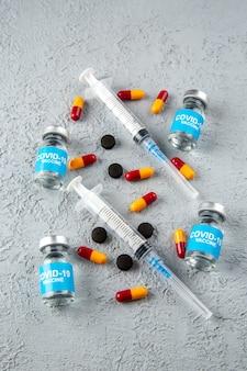 회색 모래 배경에 covid-백신 및 다양한 캡슐 빈 주사기의 수직 보기