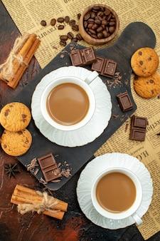 古い新聞クッキーシナモンライムチョコレートバーの木製まな板上のコーヒーの垂直方向のビュー