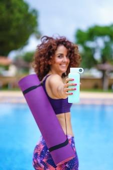 水のボトルを保持しているヨガの衣装に身を包んだ巻き毛の女性の垂直方向のビュー、ボトルに焦点を当てます。水分補給とフィットネスのライフスタイル。夏の運動と健康的なスポーツ習慣。