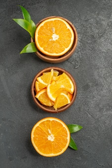 黒いテーブルの上の新鮮なレモンの葉と花を半分にスライスしたカットの垂直方向のビュー