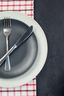 검은색 바탕에 여유 공간이 있는 빨간색 벗겨진 수건에 어두운 회색 색상과 흰색 빈 접시에 설정된 칼 붙이의 수직 보기