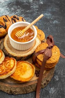 暗いテーブルの上にクロワッサン パンケーキ クッキー蜂蜜を積み上げたおいしい朝食の垂直方向のビュー