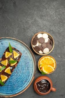 Вертикальный вид вкусного торта, украшенного лимоном и шоколадом, с другим печеньем на темном столе