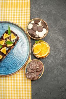 Вертикальный вид вкусного торта на желтом полосатом полотенце и печенья на черном столе