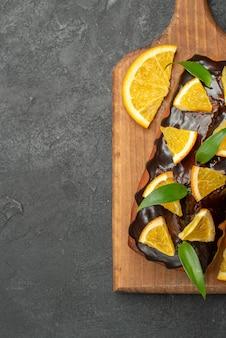 黒いテーブルのまな板にレモンとチョコレートで飾られたおいしいケーキの垂直方向のビュー 無料写真