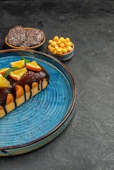 青いトレイのおいしいケーキと暗い背景のビスケットの垂直方向のビュー
