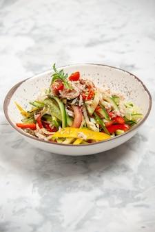 ステンドグラスの白い表面に野菜とおいしいチキンサラダの垂直図