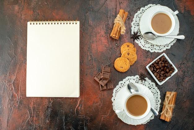 混合色の背景に白いカップクッキーシナモンライムチョコレートバーとノートブックのおいしいコーヒーの垂直方向のビュー