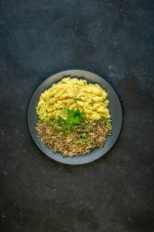 Вертикальный вид вкусного ужина с картофельным пюре и мясом на тарелке на черном фоне со свободным пространством