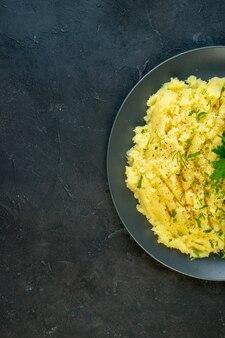 Вертикальный вид вкусного ужина с картофельным пюре и мясом на тарелке слева на черном фоне со свободным пространством