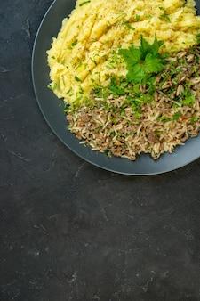 Вертикальный вид вкусного ужина с картофельным пюре и мясом на тарелке сверху на черном фоне со свободным пространством