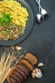 Вертикальный вид вкусного ужина с мясом и картофельным пюре на серой тарелке, ломтики хлеба, набор столовых приборов с чесночным шипом на черном фоне