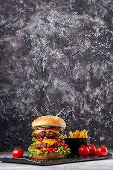 灰色の氷の表面の黒い板においしい自家製サンドイッチとフライドポテトケチャップの垂直方向のビュー