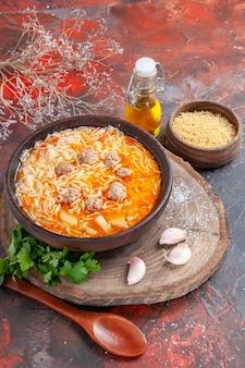 어두운 배경에 나무 커팅 보드 그린 오일 병 숟가락 마늘에 닭고기와 함께 맛있는 국수 수프의 수직 보기