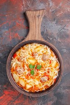 어두운 배경에 나무 커팅 보드에 닭고기와 함께 맛있는 국수 수프의 수직 보기