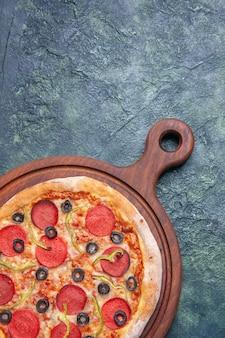 紺色の表面の右側にある木製のまな板においしいピザの垂直方向のビュー