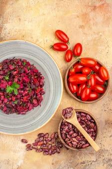 ミックスカラーテーブルの上の鍋とトマトの内側と外側のビートルートと豆と豆のおいしいサラダの垂直方向のビュー