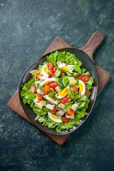黒緑ミックス色の背景に木製まな板に多くの新鮮な食材とおいしいサラダの垂直方向のビュー