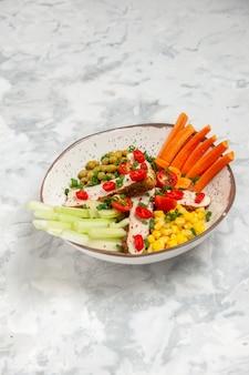 Вертикальный вид вкусного салата с различными ингредиентами на тарелке на белой поверхности
