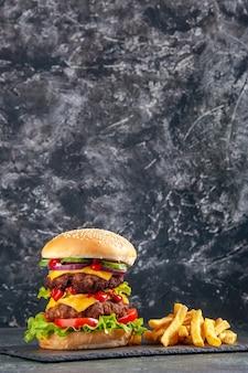 Вертикальный вид вкусного сэндвича и картофеля на подносе темного цвета на черной поверхности
