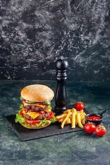 Вертикальный вид вкусного сэндвича и жареного перца на темном подносе с помидорами на черной поверхности